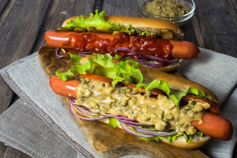 两个自创热狗用在木桌上的调味汁 库存照片