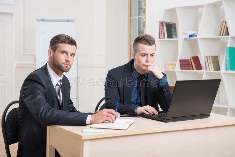 两个英俊的商人在运作在一些的办公室 库存照片