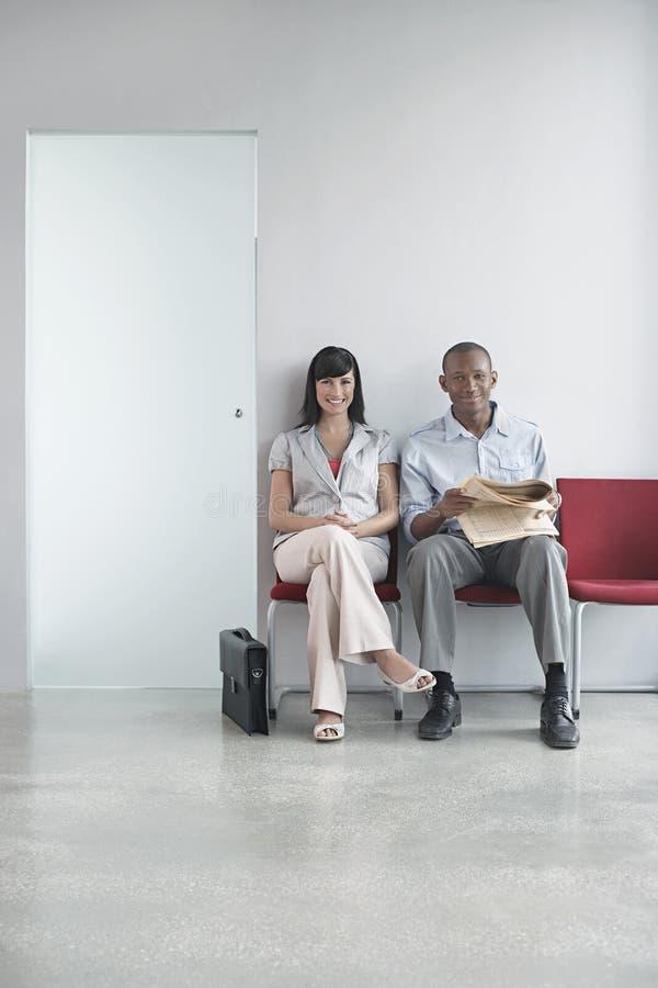 两个董事坐在走廊的椅子 免版税图库摄影