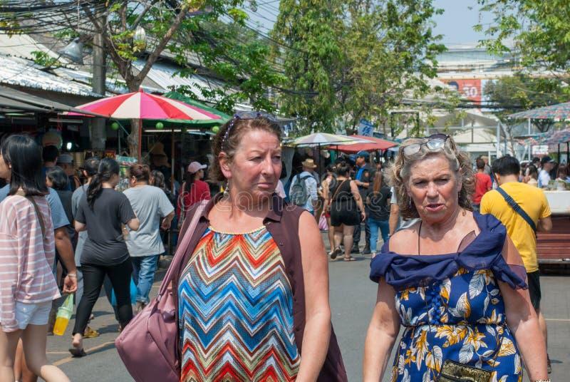 两个西方人成熟夫人似乎是朋友一起走和谈话在Chatuchak周末市场上 免版税库存图片