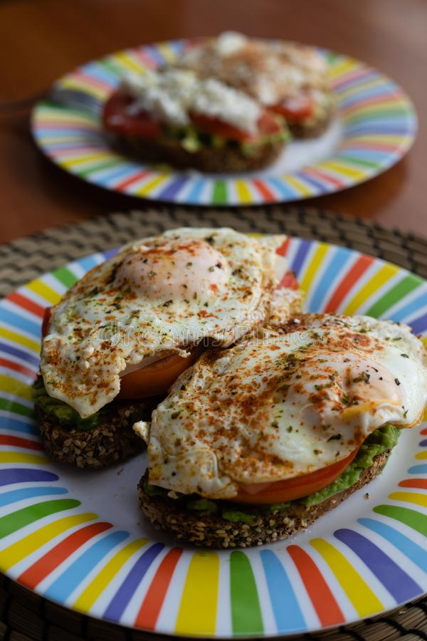 两个谷物面包切片用鲕梨、蕃茄和荷包蛋在上面,提出在一块五颜六色的板材在一顿木桌鲜美早餐 免版税库存图片