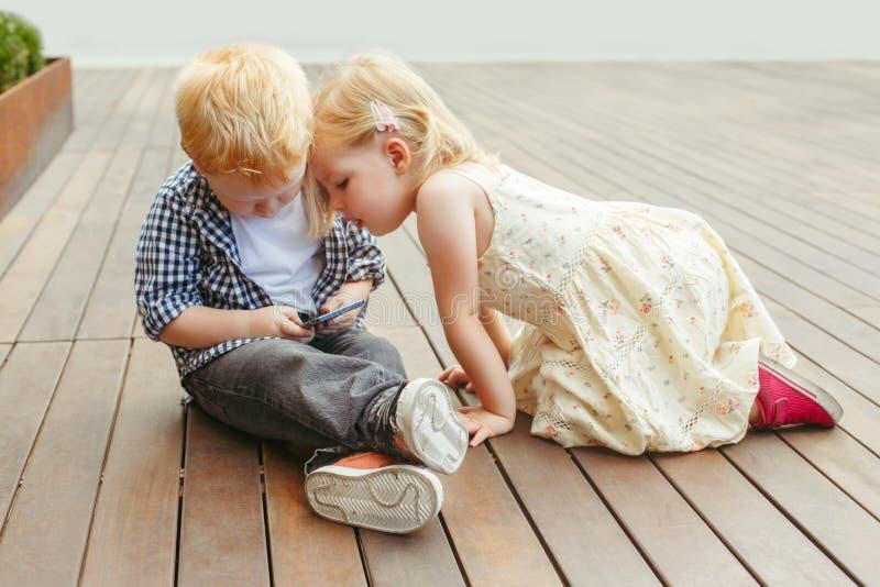 两个逗人喜爱的可爱的白白种人小孩一起坐和打比赛的男孩和女孩在细胞手机数字式片剂 图库摄影