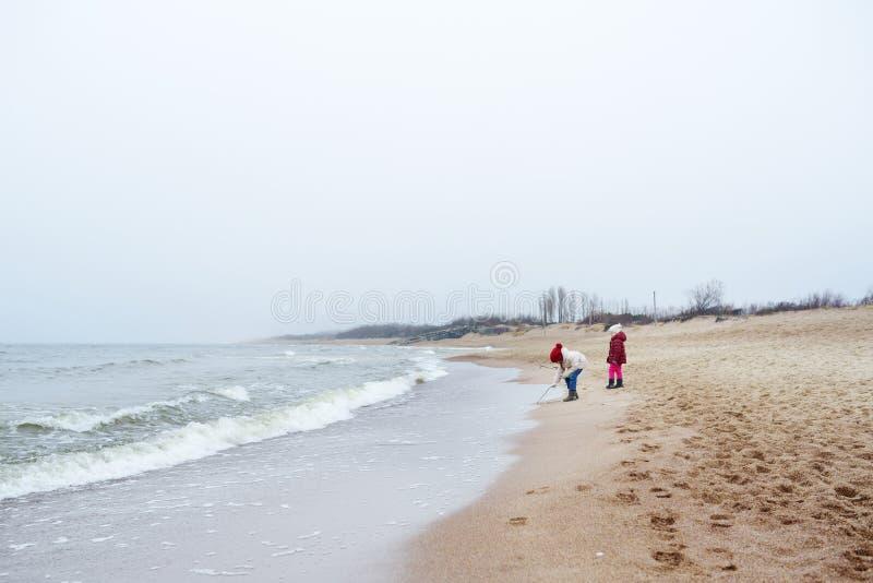 两个逗人喜爱的妹获得乐趣一起在冬天海滩在冷的冬日 使用由海洋的孩子 免版税图库摄影