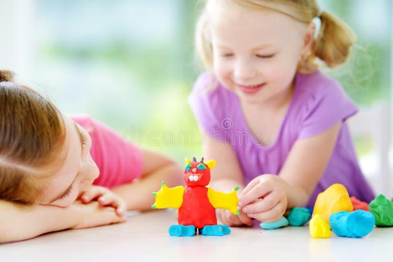 两个逗人喜爱的妹获得乐趣与五颜六色的雕塑黏土一起在托儿 在家铸造创造性的孩子 免版税库存图片