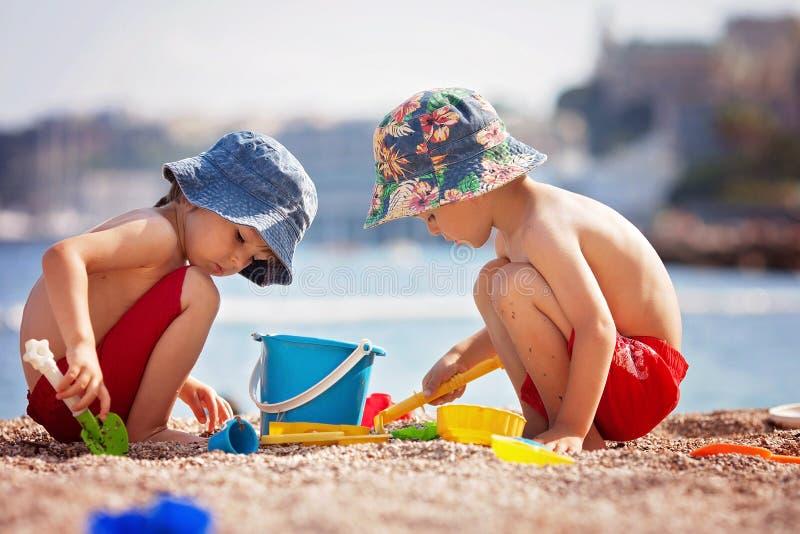 两个逗人喜爱的孩子,使用在海滩的沙子 库存照片