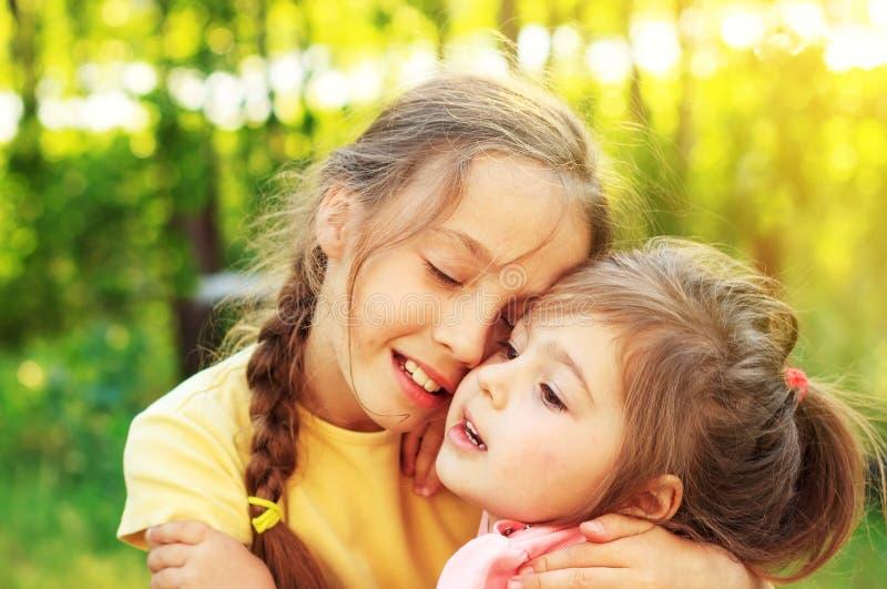 两个逗人喜爱的小女孩在春天庭院里拥抱室外 一起花费时间的孩子姐妹 免版税库存图片