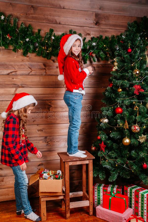 两个逗人喜爱的小孩女孩装饰圣诞树户内 库存图片