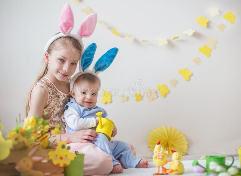 两个逗人喜爱的小孩男孩和女孩佩带的兔宝宝耳朵 库存图片