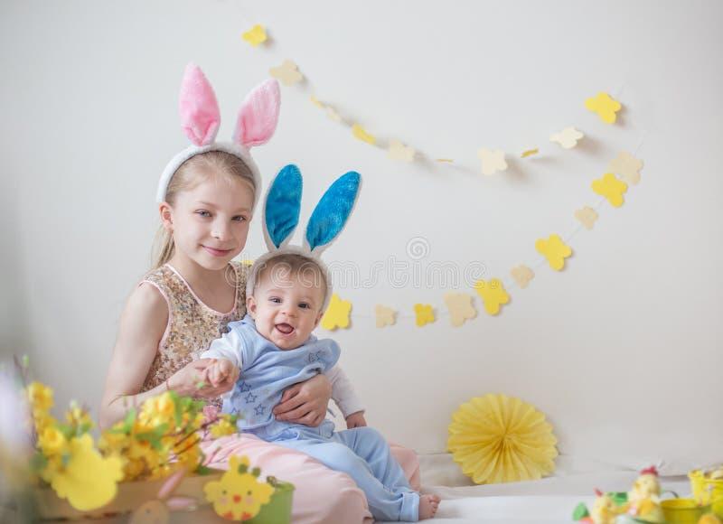 两个逗人喜爱的小孩男孩和女孩佩带的兔宝宝耳朵 图库摄影