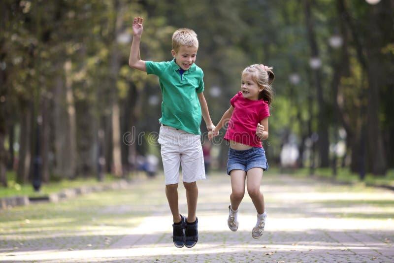 两个逗人喜爱的年轻滑稽的微笑的孩子,女孩和男孩、兄弟和姐妹,跳跃和获得在被弄脏的明亮的晴朗的公园胡同的乐趣 库存图片