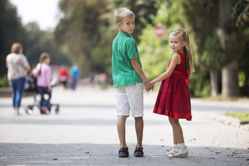 两个逗人喜爱的年轻白肤金发的微笑的握在被弄脏的明亮的晴朗的夏天公园胡同的孩子、女孩和男孩、兄弟和姐妹手 库存图片