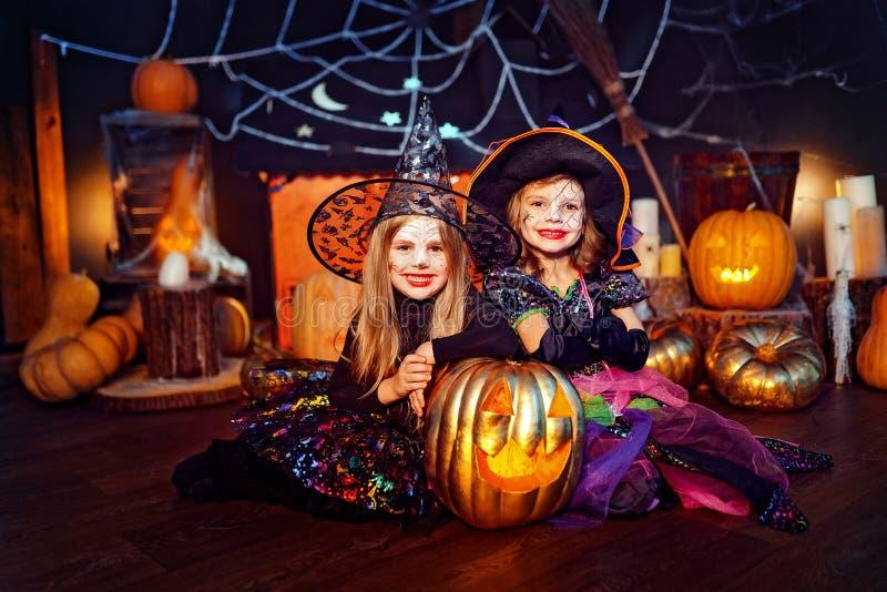 两个逗人喜爱的滑稽的姐妹庆祝假日 狂欢节的快活的孩子在万圣夜打扮准备好 免版税库存照片