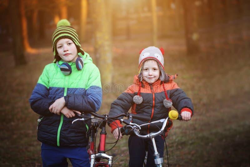 两个逗人喜爱的男孩,兄弟姐妹孩子,获得在自行车的乐趣在同水准 免版税库存图片