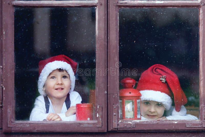 两个逗人喜爱的男孩,看通过窗口,等待的圣诞老人 库存照片
