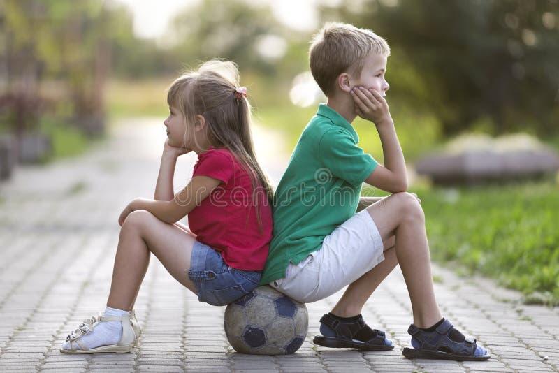 两个逗人喜爱的白肤金发的孩子、微笑的男孩和长发女孩外形画象坐在空的晴朗的郊区的足球铺了 免版税库存照片