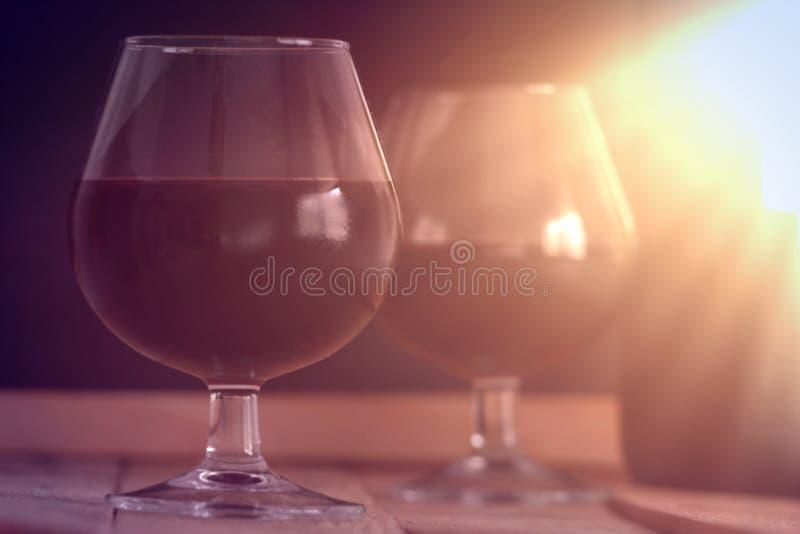 两个酒杯和一个瓶在一张木桌上反对黑背景 轻的星期日 免版税图库摄影
