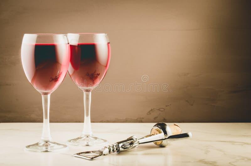 两个酒杯和螺旋式前进/两个红酒酒杯和木拔塞螺旋在棕色背景 r 免版税库存图片