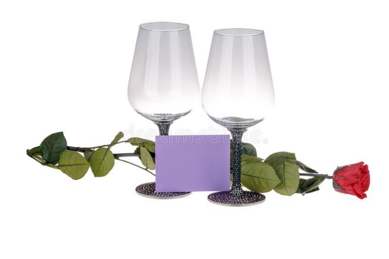 两个酒杯特写镜头与红色玫瑰和愿望卡片的 免版税库存图片