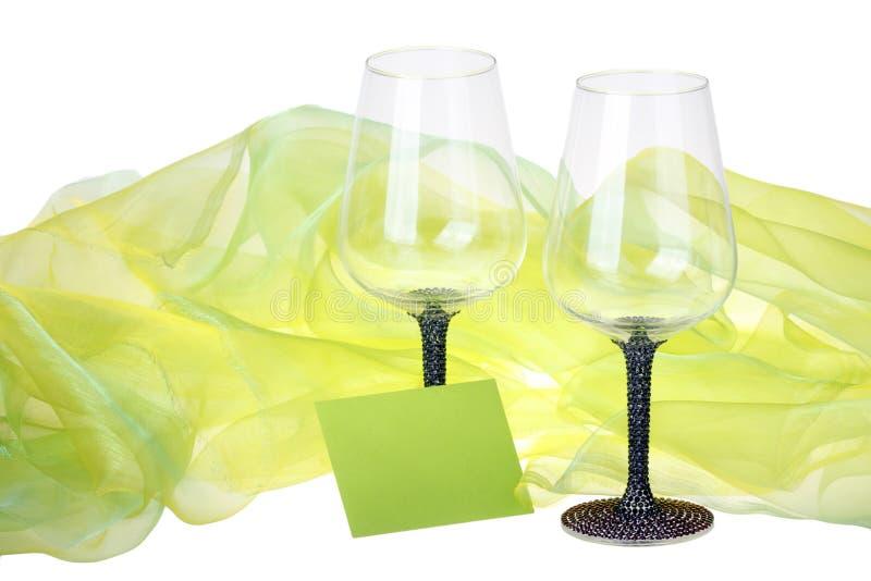 两个酒杯特写镜头与绿色天鹅绒围拢的愿望卡片的 免版税库存图片
