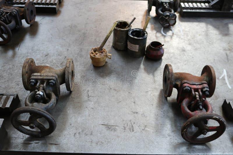 两个金属老门闩,管子配件,有石墨油膏的,在一张大铁桌上的solidol罐头在工厂 免版税库存照片