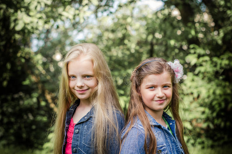 两个长发青春期前的女孩画象,当微笑时 库存图片