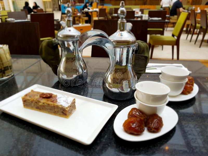 两个阿拉伯咖啡罐,杯子,日期,在桌上的蛋糕在咖啡馆 库存图片