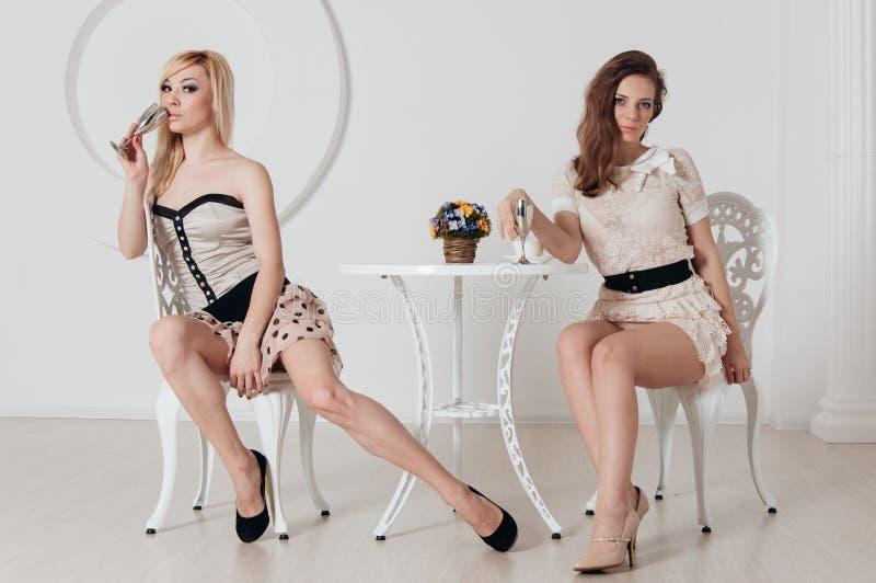 两个难以置信的女孩坐在桌上 免版税库存照片