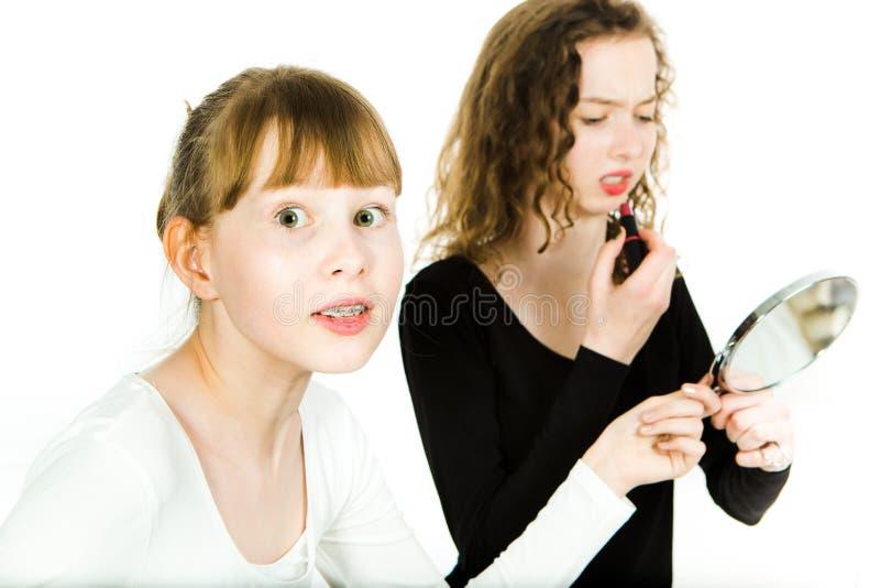 两个青少年女孩,一与两个青少年女孩,一个与括号,在青春期得到镜子的年龄讲价做a组成讲价 免版税库存图片