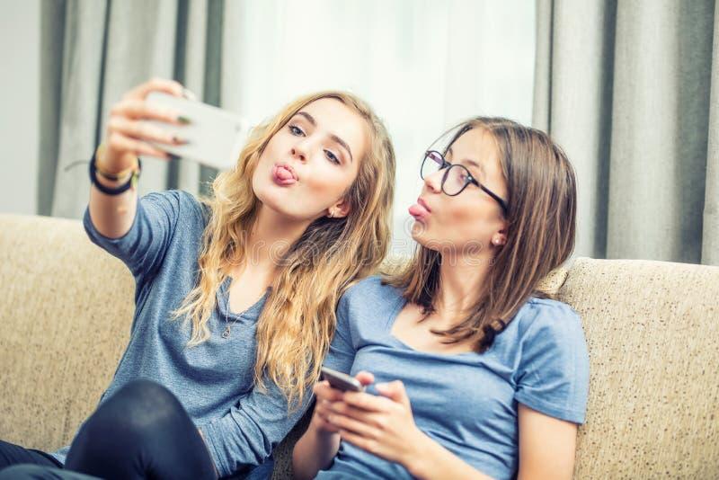 两个青少年的女孩一起微笑并且采取selfie 他们从他们的舌头做鬼脸 免版税图库摄影