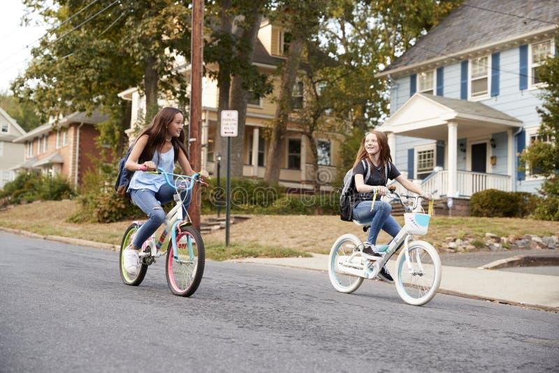 两个青少年的女朋友在一条静街的自行车乘坐过去 库存照片
