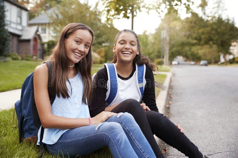 两个青少年的女朋友坐在看对照相机的路旁 库存照片