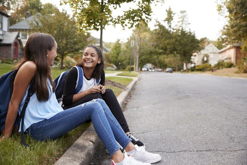 两个青少年的女朋友坐谈话在路旁 库存照片