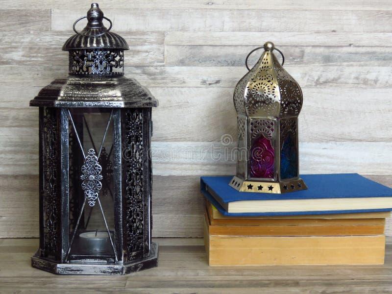 两个非常老银色灯笼和堆在被漂白的橡木背景的旧书 库存图片