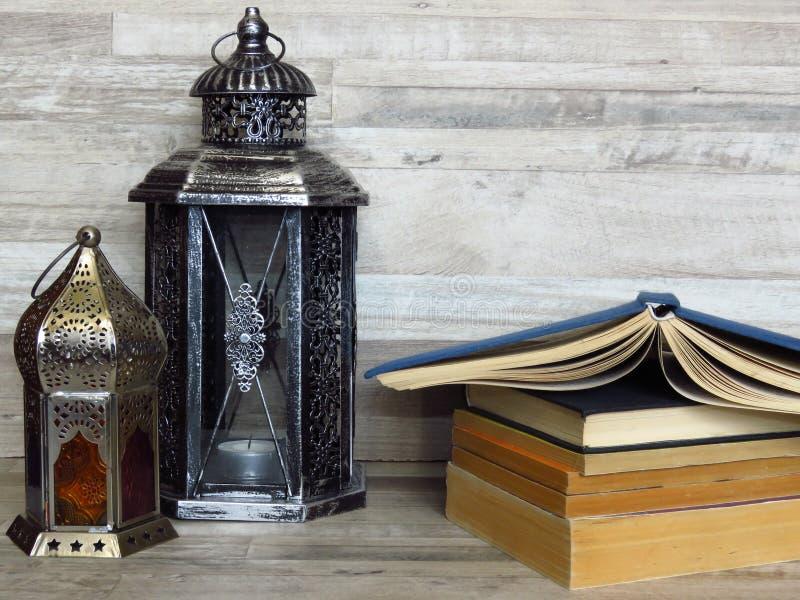 两个非常老银色灯笼和堆在被漂白的橡木背景的旧书 免版税库存照片