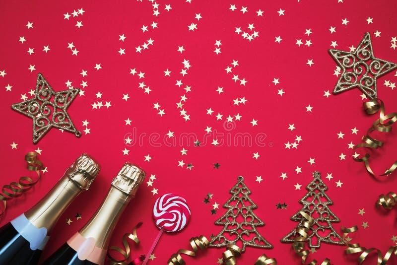 两个香槟瓶、圣诞节装饰品、糖果和五彩纸屑星在红色背景 圣诞节背景,顶视图,拷贝空间 免版税图库摄影