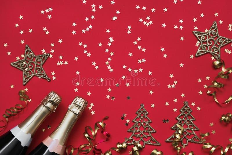 两个香槟瓶、圣诞节装饰品和五彩纸屑星在红色背景 圣诞节背景,顶视图,拷贝空间 免版税库存照片