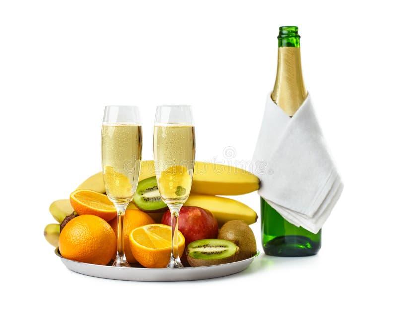 两个香槟玻璃和瓶用果子在盘子 库存照片