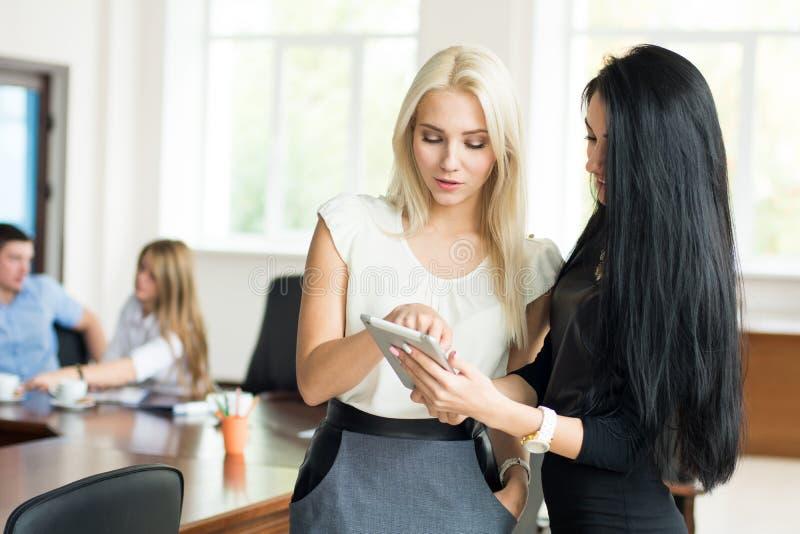 两个年轻人有片剂计算机的女商人在d的办公室 库存图片
