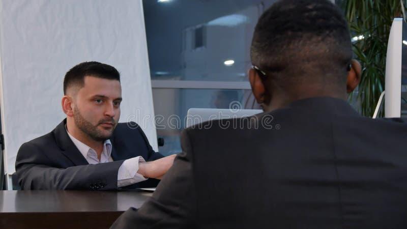 两个年轻商人谈论项目在会议上 图库摄影