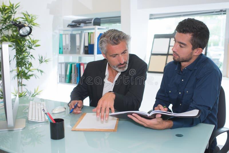 两个年轻商人谈话在办公室 免版税图库摄影