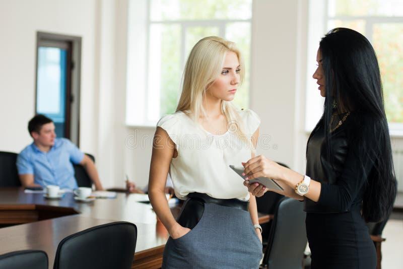 两个年轻女商人白肤金发和深色与片剂compu 库存照片