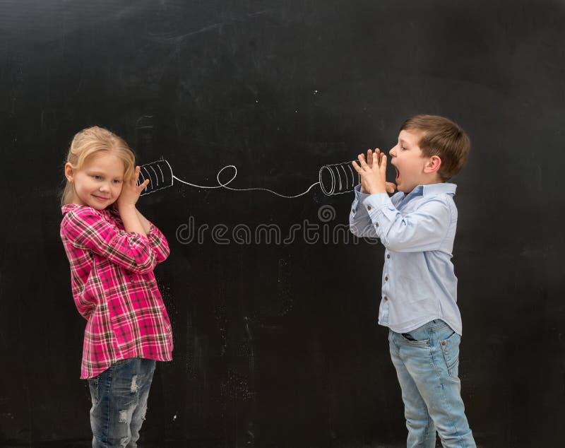 两个滑稽的孩子谈话在自制被画的电话 免版税图库摄影