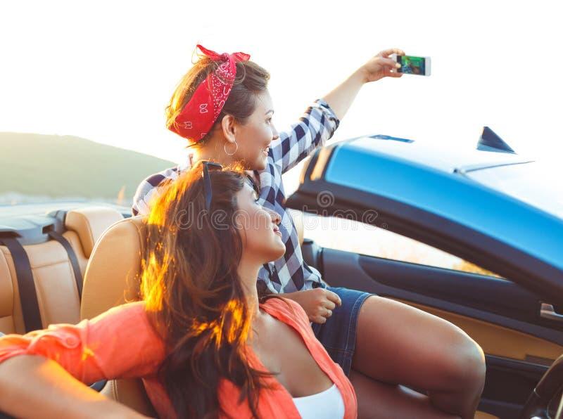 两个年轻美丽的女孩做着在敞篷车的selfie 免版税库存图片