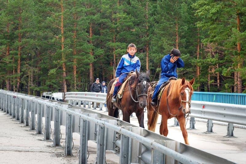 两个Buryat男孩在桥梁骑马在Arshan 俄国 库存照片