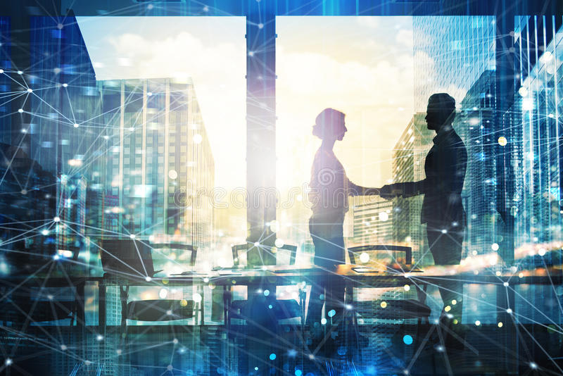 两买卖人握手在有网络作用的办公室 合作和配合的概念 库存图片