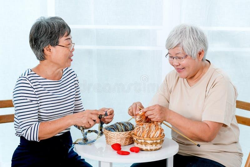 两亚裔年长妇女坐椅子和有编织,也与微笑一起的谈话的活动在阳台前面 免版税库存图片