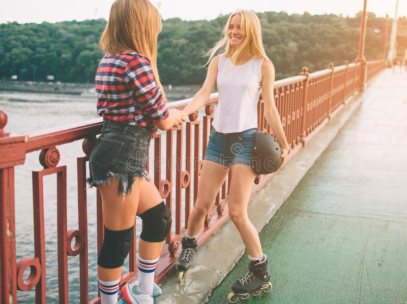 两亭亭玉立和性感的少妇和溜冰鞋 一位女性有轴向冰鞋,并且其他有方形字体冰鞋 女孩 图库摄影