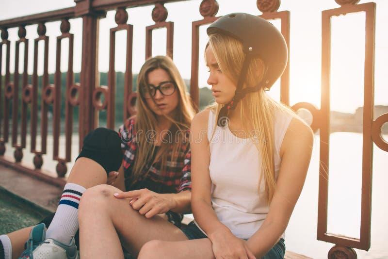 两亭亭玉立和性感的少妇和溜冰鞋 一位女性有轴向冰鞋,并且其他有方形字体冰鞋 女孩 库存照片