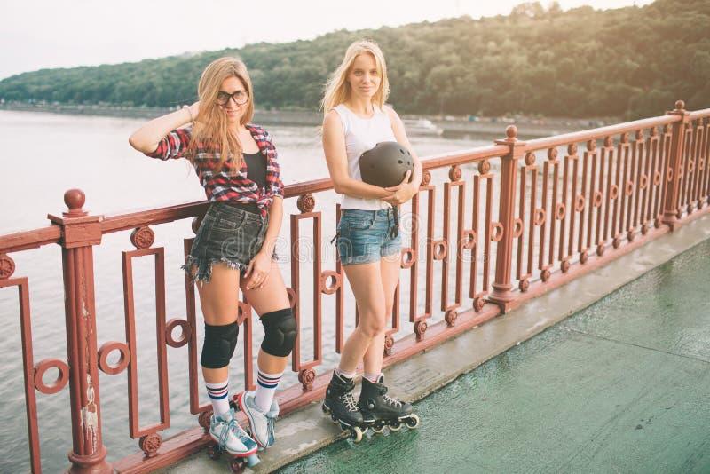 两亭亭玉立和性感的少妇和溜冰鞋 一位女性有轴向冰鞋,并且其他有方形字体冰鞋 女孩 免版税库存图片