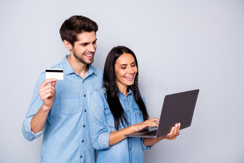 两人合作制作手提信用卡笔记本电脑的喜悦时尚商务情侣照片 免版税图库摄影